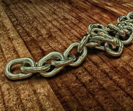 Realistic 3D model of a metal chain on the wooden floor. 3d rend Royalty Free Stock Images