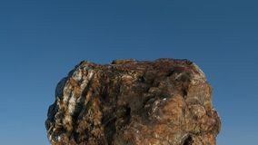Rock /mountain in front of blue sky. Realistic 3D rendering of a rock /mountain in front of blue sky Royalty Free Stock Image
