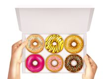Realistic Donuts In Box In Hands. Realistic colorful donuts with sprinkles, glaze and sesame seeds in open white box in hands vector illustration Stock Image