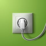 Realistic electric white socket and plug on green Stock Image