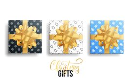 Realistic gifts. Christmas gift packages with gold bows and winter patterns.  Stock Images