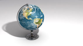 A realistic globe on a chrome pedestal over white A Royalty Free Stock Photography