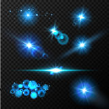 Realistic glow blue light effects. Lens flare set. Realistic glowing sparkles particles effects on dark transparent grid Stock Images