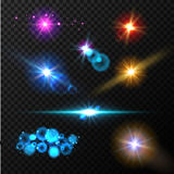 Realistic glow light effects. Lens flare set. Realistic glowing sparkles particles effects on dark transparent grid Royalty Free Stock Photography
