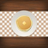 Realistic pancake with a piece of butter on a white plate closeup on wood background, top view. Design template for. Breakfast, food menu and homestyle concept Royalty Free Stock Image