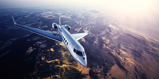 Realistic photo of silver generic design private Jet flying over the mountains. Empty blue sky with sun at background Royalty Free Stock Images