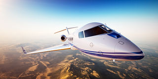 Realistic photo of white generic design private Jet flying over the mountains. Empty blue sky with sun at background. Business Travel by modern Luxury Aircraft Stock Photos