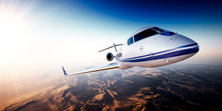 Realistic photo of white generic design private Jet flying over the mountains. Empty blue sky with sun at background Royalty Free Stock Photography