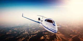 Realistic photo of white generic design private Jet flying over the mountains. Empty blue sky with sun at background Stock Image