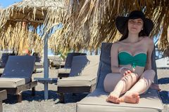 Realistic portrait of a young woman in a green swimsuit and hat, sitting on a chaise longue under a straw umbrella. The concept of recreation, summer stock photos