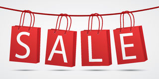 Realistic red shopping bags hanging on rope with text sale on grey background Stock Images