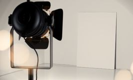 Searchlight gives light on white canvas, 3d rendering. Realistic searchlight gives light on white canvas and wall, another spotlight is out of the focus, 3d Stock Photos