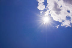 Realistic shining sun with lens flare. Blue sky with clouds Royalty Free Stock Photography