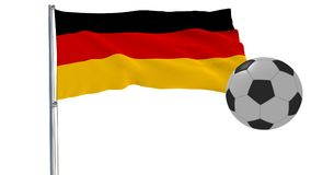 A realistic soccer ball flies around the realistically fluttering flag of Germany on a white background, 3d rendering. Royalty Free Stock Images