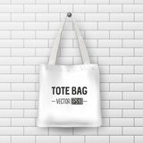 Realistic vector white textile tote bag. Closeup on brick wall background. Stock Image