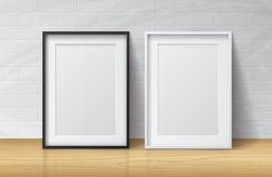 Realistic White and Black Blank Picture frame, standing on Light. Wood Floor at Stock Photography