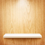 Realistic white shelf on wooden wall Royalty Free Stock Image