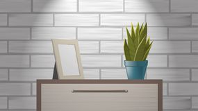 Realistic woden picture frame mock up and green home plant standing on commode. Royalty Free Stock Photo