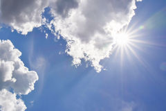 Realistische glänzende Sonne mit Blendenfleck Blauer Himmel mit Wolken Stockbild