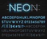 Realistisches Neonalphabet auf einem Hintergrund der schwarzen Backsteinmauer Blauer glühender Guss Alle verschiedenen Grafiken s Stockbilder