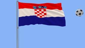 Realistisk fladdraflagga av Kroatien och fotbollbollen som omkring flyger på en blå bakgrund, tolkning 3d Royaltyfria Foton