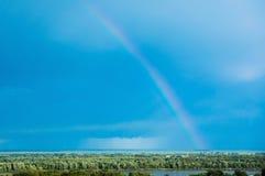 Realistisk regnbåge på blå himmel Royaltyfri Bild