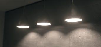 Realistiska hängande ljus i konkret rum med den mjuka fokusen Royaltyfria Bilder