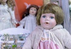 Realistiskt behandla som ett barn - dockan med blåa ögon i en beige tröja och en rosa klänning royaltyfri fotografi