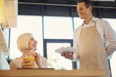 Realitet åldras kvinna som väntar på hennes frukost arkivbild