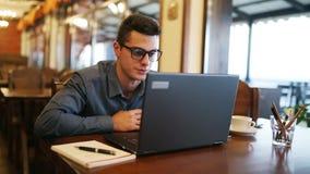 Realitet som ler den caucasian mannen i exponeringsglas som talar på videokonferensappellpratstund med en bärbar dator i kafé Hög stock video