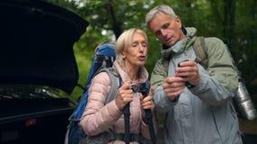 Realiteten åldrades par av turister som vilar i skogen arkivfilmer