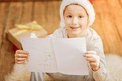 Realiteten var besvärad barnet som visar teckningen av julträdet Arkivfoton