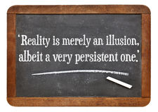 Reality as illusion quote. Reality is merely an illusion, albeit a very persistent one - a quote from Albert Einstein on a vintage slate blackboard royalty free stock image