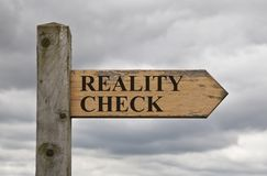 Reality Check Wooden Sign. Grungy wooden reality check sign on a sign post against cloudy sky Royalty Free Stock Photo