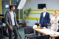 Realizador de cinema que discute o plano do filme com os atores fotos de stock