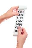 Realizar da mulher em seu rolo das mãos de papel com recibo impresso Euro- Fotos de Stock Royalty Free