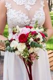 Realizar da noiva em seu ramalhete do casamento das mãos foto de stock royalty free