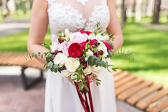 Realizar da noiva em seu ramalhete do casamento das mãos fotografia de stock