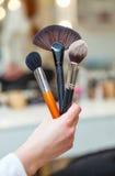 Realizar de artista de composição no seu as escovas da mão três feitas de cerdas naturais para o pó, fundação e coram Fotografia de Stock