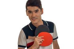 Realizar de homem novo em suas raquetes da mão para o tênis de mesa e um close-up de um sorriso isolaram-se no fundo branco Fotografia de Stock Royalty Free