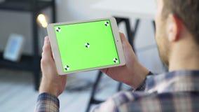 Realizar do homem de negócios nas mãos fecham-se acima e usam-se o dispositivo com a tela do verde do toque video estoque