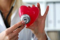Realizar fêmea do doutor da medicina no coração vermelho do brinquedo das mãos Imagem de Stock