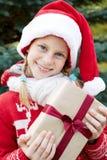 Realizar felizes da criança no presente de Natal das mãos Foto de Stock Royalty Free