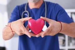 Realizar masculino do doutor no coração do vermelho dos braços Fotos de Stock Royalty Free