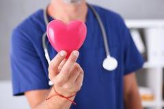 Realizar masculino do doutor no coração do vermelho dos braços Fotos de Stock