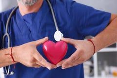 Realizar masculino do doutor no coração do vermelho dos braços Imagem de Stock Royalty Free