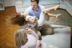 Realizar nos braços Família que joga em casa Foto de Stock