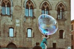 Realizzi i loro sogni - prova del bambino per scoppiare una bolla di sapone fotografia stock libera da diritti