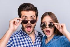 Realmente?! Due amanti colpiti giovani sono stupiti con gli occhi spalancati, i mouthes, occhiali da sole di riparazione, in un a Fotografia Stock Libera da Diritti