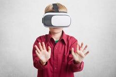 Realtà aumentata, bambini e concetto di spettacolo Il piccolo bambino in cuffia avricolare virtuale gode di belle ed immagini emo Immagine Stock Libera da Diritti